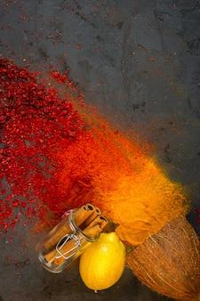 Spezie colorate superiori con bastoncini di cannella cocco lemonnd su fondo nero