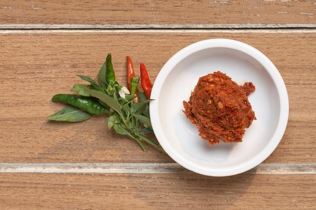 Spezie della tailandia in tazza bianca su di legno per la cottura degli alimenti tailandesi, peperoncino curry thai tood