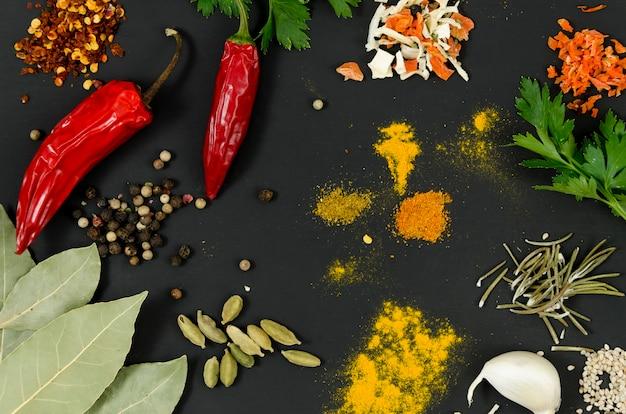 Spezie e peperoncini rossi di vista superiore su fondo nero