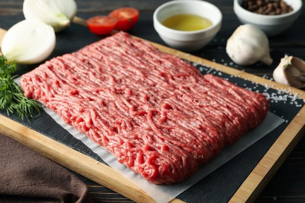 Spezie e tagliere con carne tritata su alto di legno e vicino