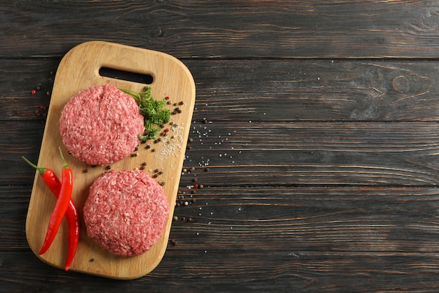 Spezie e tagliere con carne tritata sulla vista di legno e superiore