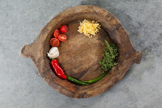 Spezie e verdure in ciotola di legno