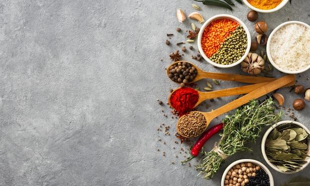 Spezie ed erba, riso e vari fagioli con copyspace sulla vista superiore del backgraund del wite