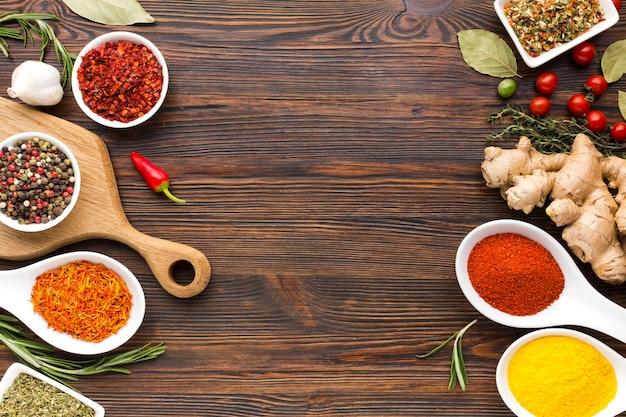 Spezie ed erbe aromatiche in ciotole e cucchiaio con copia-spazio