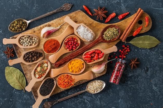 Spezie ed erbe aromatiche per cucinare su un tagliere e in cucchiai di legno