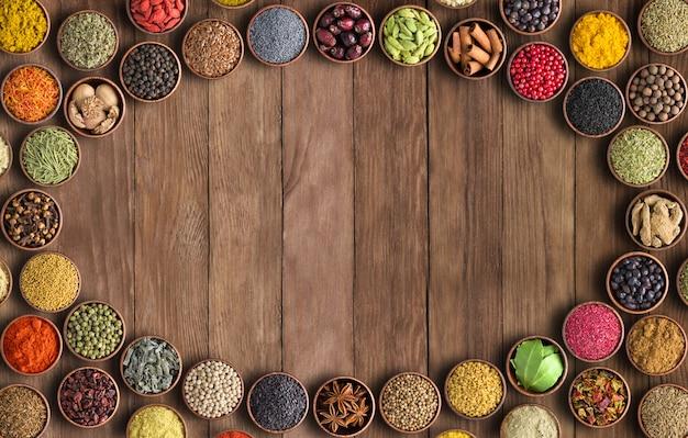 Spezie ed erbe aromatiche su ciotole di legno