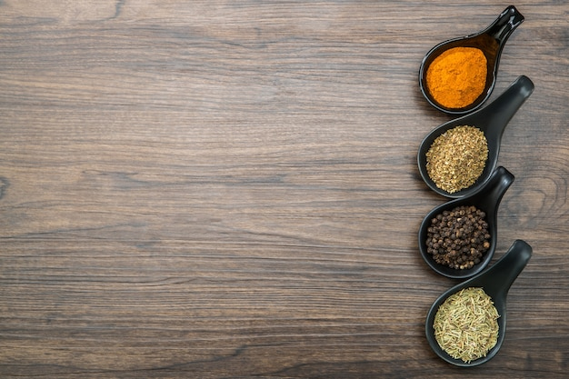 Spezie ed erbe differenti in cucchiai o ciotole su un fondo di legno marrone