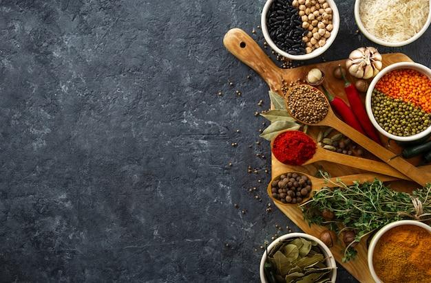 Spezie, erbe, riso e vari fagioli e condimenti per la cottura sul backgraund scuro con copyspace vista dall'alto