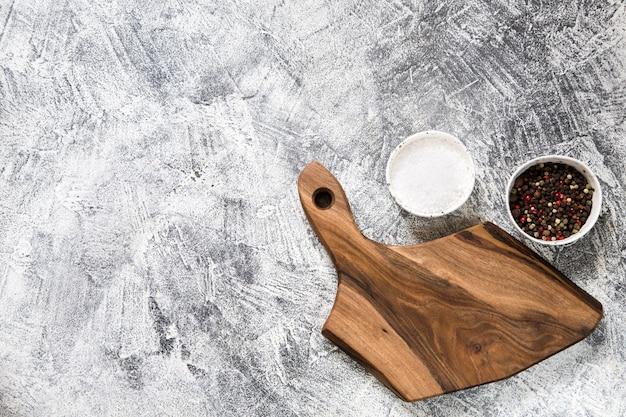 Spezie, erbe, tagliere di legno per cucinare. tagliere su sfondo grigio cemento.
