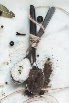 Spezie in cucchiai. di sale e pepe. tavolo in marmo di pietra. tonalità rustica dai colori vintage