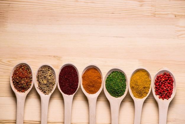 Spezie in cucchiai e sul tavolo di legno