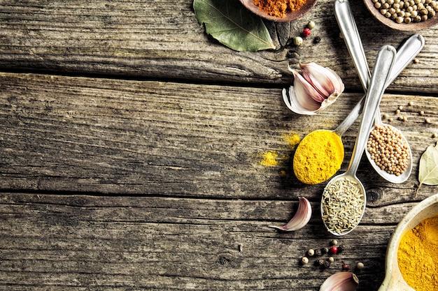 Spezie in cucchiai su fondo in legno