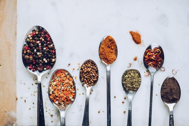 Spezie in diversi cucchiai sul tavolo di pietra di marmo. tonalità rustica dai colori vintage