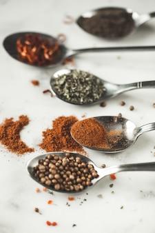 Spezie in diversi cucchiai sul tavolo di pietra di marmo.