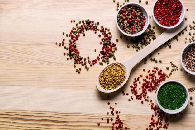 Spezie in piatti e cucchiai sulla tavola di legno