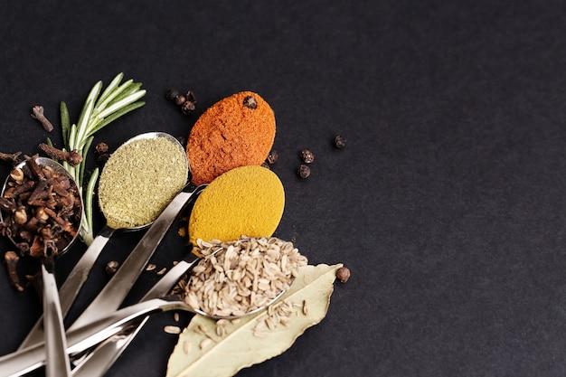 Spezie in polvere sul tavolo nero, vista dall'alto
