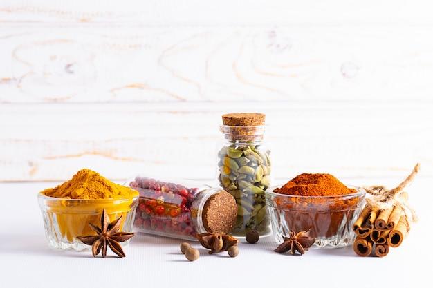 Spezie indiane aromatiche organiche su fondo di legno bianco con lo spazio della copia per la vostra progettazione.