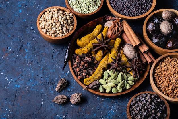 Spezie indiane di riscaldamento a secco dentro sul piatto per il pasto di inverno di autunno su calcestruzzo blu scuro.