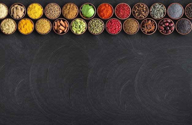 Spezie indiane sul fondo nero della tavola. lavagna per alimenti con condimenti