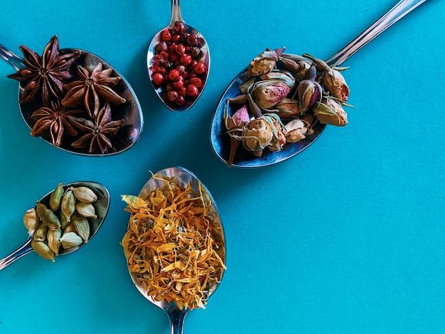 Spezie nella vista superiore dei cucchiai e nel fondo blu. spezie a base di erbe per gin tonic.