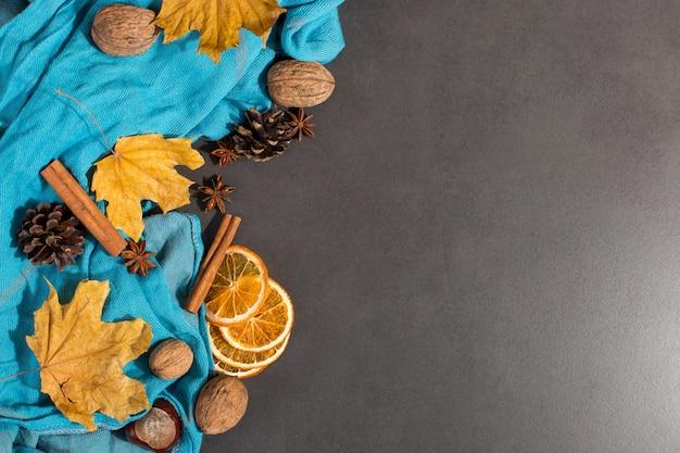 Spezie, una sciarpa, noci, foglie secche e arance su un tavolo di pietra. mood autunnale, un metodo per scaldarsi al freddo, copyspace.