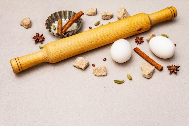 Spezie, uova, zucchero di canna, teglia per cupcake e mattarello. leggero