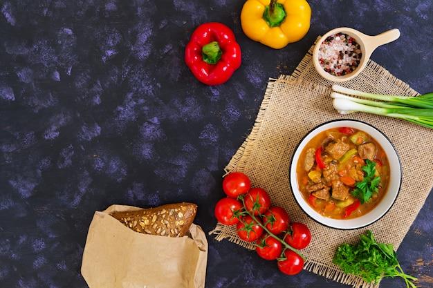 Spezzatino con carne e verdure in salsa di pomodoro sul buio