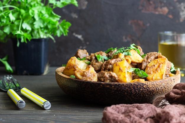 Spezzatino di carne con patate e prezzemolo in piatto di legno. stufato di carne tradizionale portoghese.