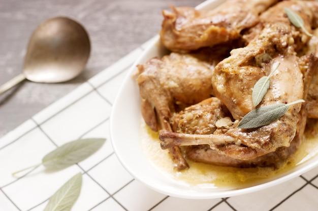 Spezzatino di coniglio in salsa di vino e panna con aggiunta di senape, aglio, timo e salvia.