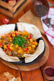 Spezzatino di manzo con patate e verdure tritate servite con lavash.