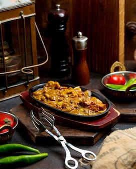 Spezzatino di manzo cotto con verdure e salsa in padella di ferro