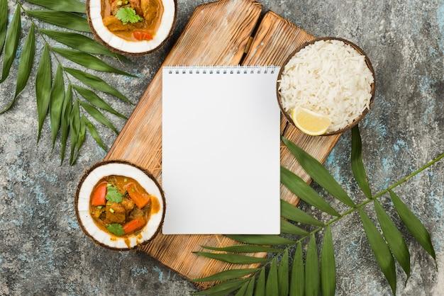 Spezzatino e riso in piatti di cocco con blocco note vuoto
