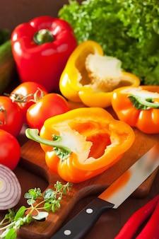 Spezzettamento del peperoncino rosso sano della cipolla dell'insalata del pomodoro al pepe delle verdure su fondo rustico