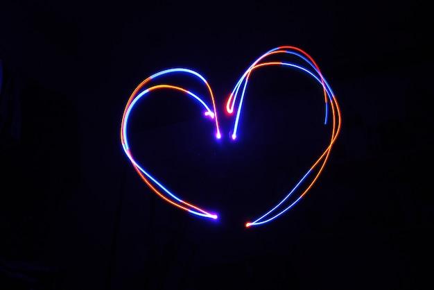 Spia della luce colorata a forma di cuore su una lunga esposizione sparata al buio.