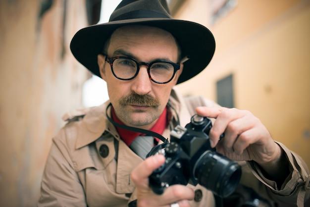 Spia o fotografo paparazzo, uomo che usa la macchina fotografica in una strada cittadina