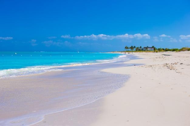 Spiaggia bianca perfetta con acqua turchese all'isola dei caraibi