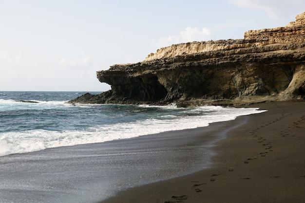 Spiaggia circondata da rocce e mare sotto la luce del sole nelle isole canarie