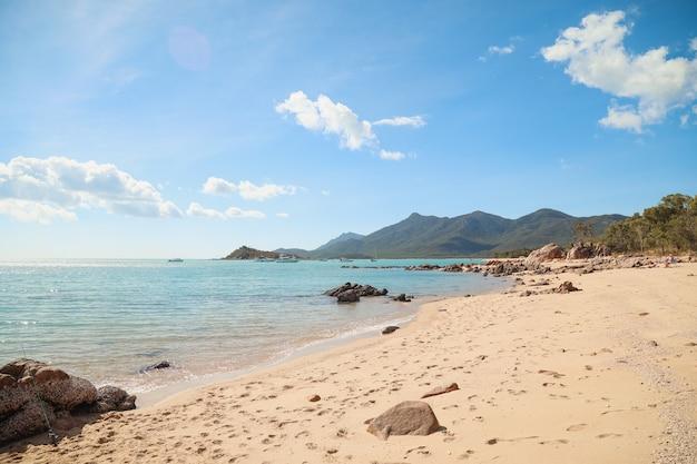 Spiaggia circondata da scogli e mare con colline ricoperte di verde