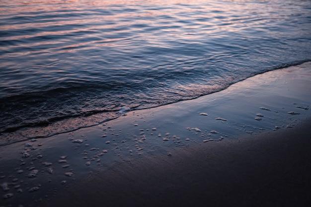 Spiaggia circondata dal mare sotto la luce del sole durante il tramonto
