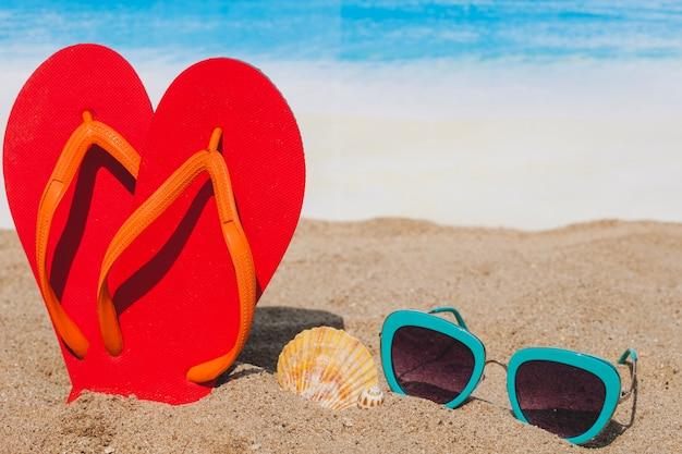 Spiaggia con flip flops, occhiali da sole e conchiglia