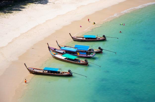 Spiaggia del curce di vista sul mare con la barca di legno turistica di estate