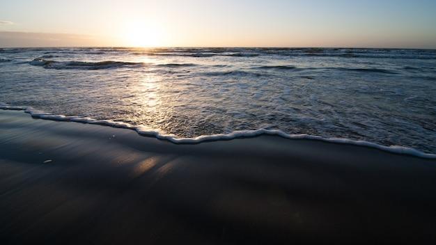 Spiaggia dell'oceano con onde luminose sopra la sabbia