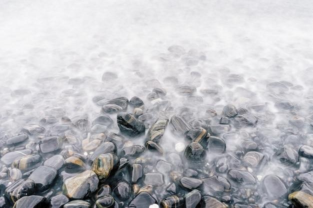 Spiaggia di ciottoli di mare con pietre multicolori, onde trasparenti con nebbia