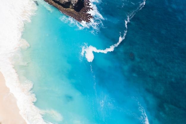 Spiaggia di kelingking sull'isola di nusa penida nel fondo dell'indonesia