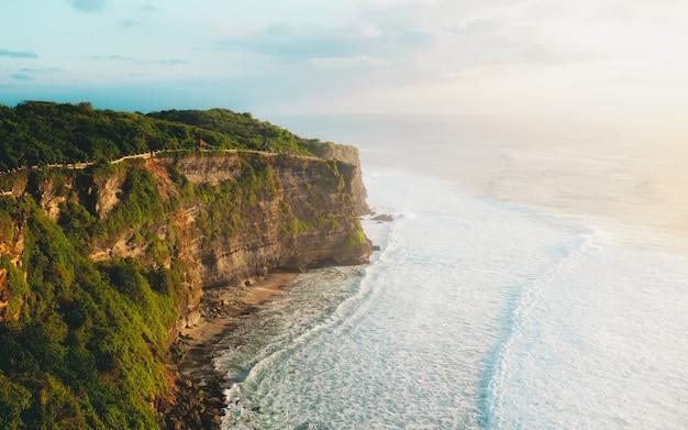 Spiaggia di roccia alta scogliera con alberi e onde sul tramonto
