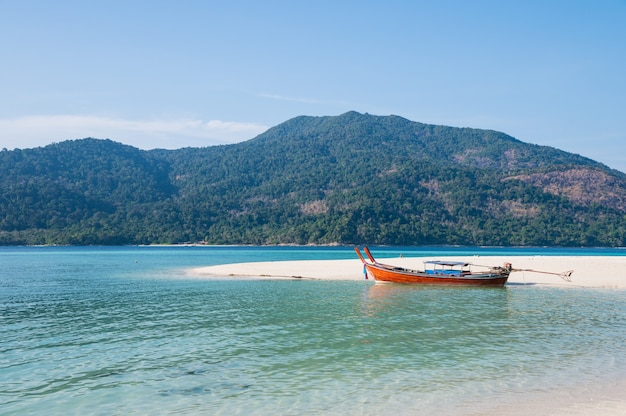 Spiaggia di sabbia bianca con barca a coda lunga in legno in mare tropicale