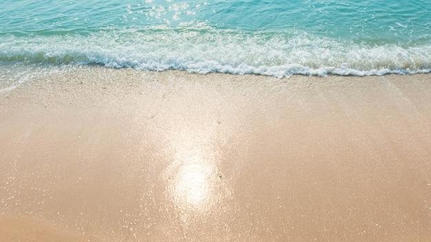 Spiaggia di sabbia blu di riflessione di luce solare delle onde di oceano
