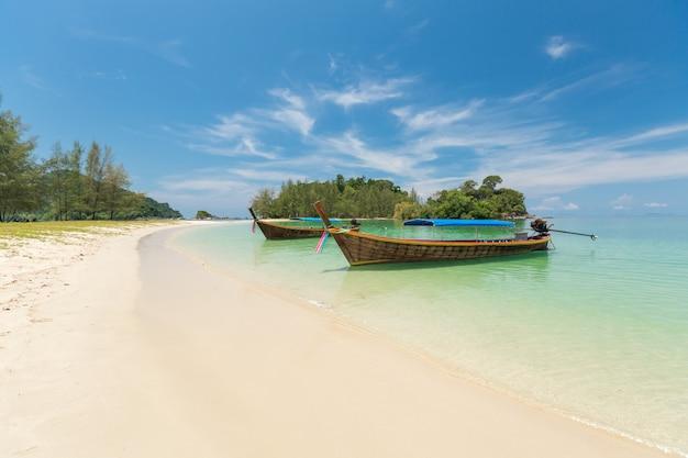 Spiaggia di sabbia e barca a coda lunga a kham-tok island (koh-kam-tok), la bellissima provincia di ranong mare, thailandia.