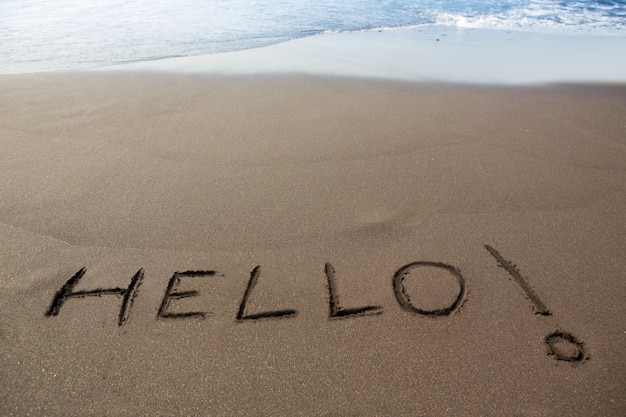 Spiaggia di sabbia marrone con scritta parola ciao
