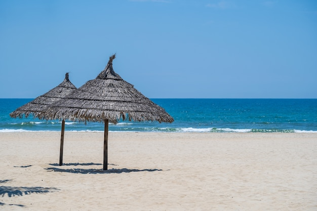 Spiaggia di sabbia tropicale e acqua di mare estiva con cielo blu e due ombrelloni di paglia